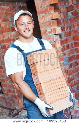 Construction worker. Mason bricklayer carrying a heavy load of red bricks