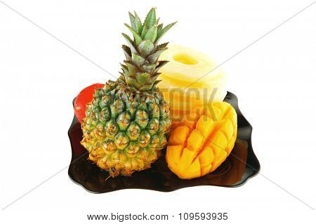 raw pineapple on black plate isolated over white background