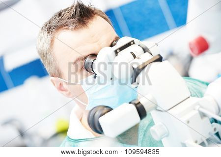 Dentistry. Dentist male doctor using microscope for operation at dentistry office