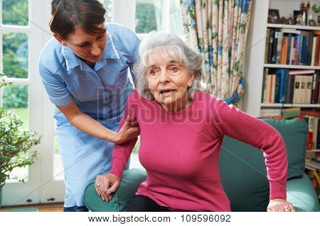 Carer Helping Senior Woman Out Of Chair