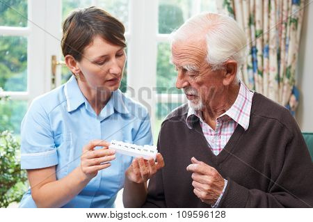 Carer Helping Senior Man With Medication
