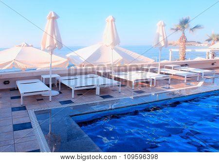 Outdoor Sun Beds Near Swimming Pool On Summer Resort