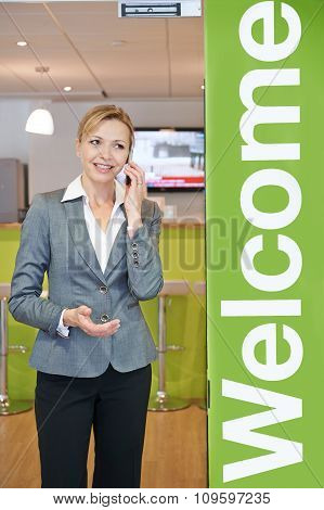 Businesswoman On Mobile Phone By Office Entrance