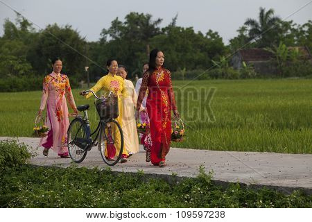 Christian Vietnamese women wearing Ao Dai while walking to the church