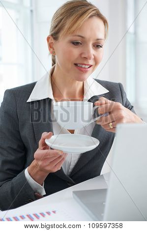 Female Executive Working At Desk With Hot Drink