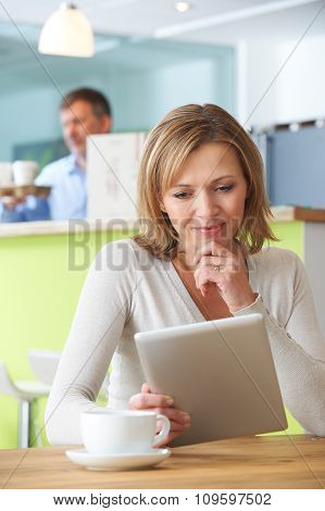 Woman Looking At Digital Tablet In Cafe