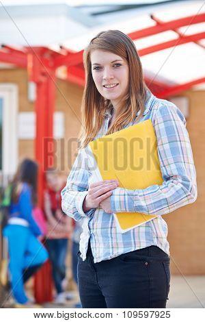 Portrait Of Teacher Standing In Playground With Folder