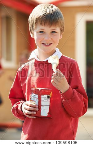 Boy In School Uniform Eating Potato Chip In Playground