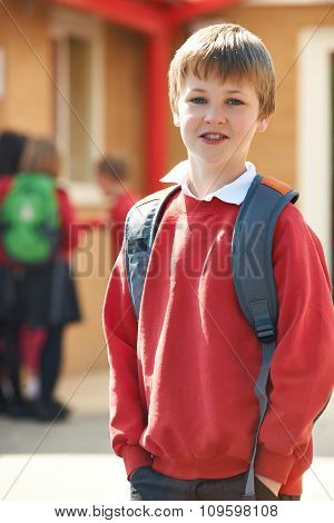 Boy Wearing Uniform Standing In School Playground