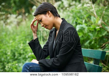 Unhappy Young Woman Sitting On Park Bench