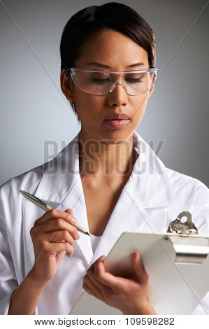 Female Scientist Writing On Clipboard