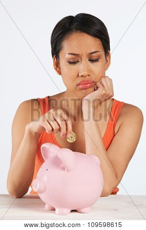 Unhappy Woman Putting Coin Into Piggy Bank