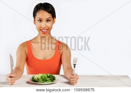Happy Woman Sitting In Front Of Lkettuce Leaves On Plate