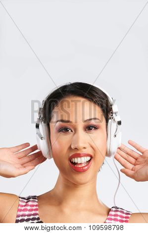 Studio Shot Of Woman Listening To Music Through Headphones