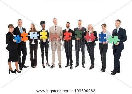 Portrait Of Happy Business Team Holding Jigsaw Pieces