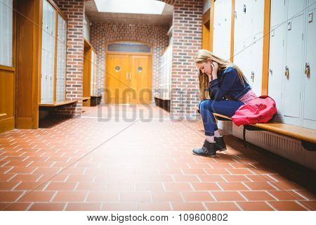 Worried student sitting and looking down at the university