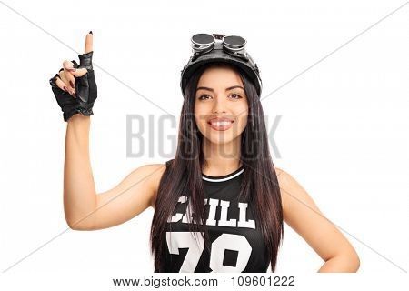 Studio shot of a young female motorcyclist pointing up with her finger isolated on white background