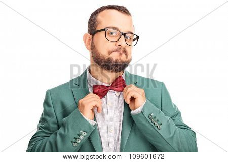 Studio shot of a cheerful young hipster adjusting his bow-tie and looking at the camera isolated on white background