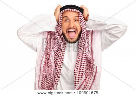 Studio shot of an outraged young Arab posing with his hands on his head isolated on white background