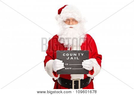 Studio shot of a criminal Santa Claus posing for a mug shot with a black board in his hand isolated on white background