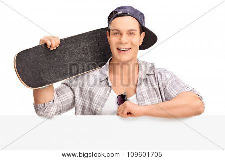 Cheerful male skater holding a skateboard and posing behind a blank billboard isolated on white background