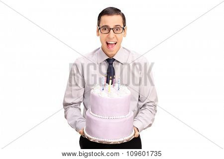 Cheerful young man holding a birthday cake and looking at the camera isolated on white background