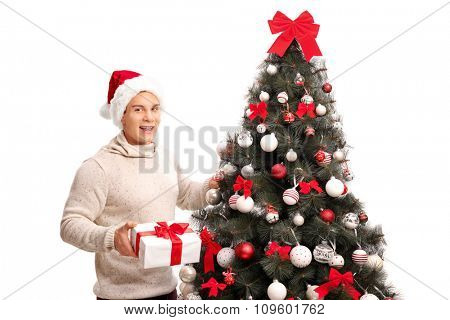 Cheerful man with Santa hat standing next to a Christmas tree and holding a present isolated on white background