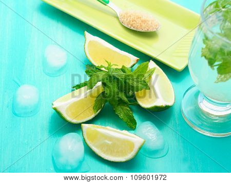 Mojito ingredients with ice on green pastel