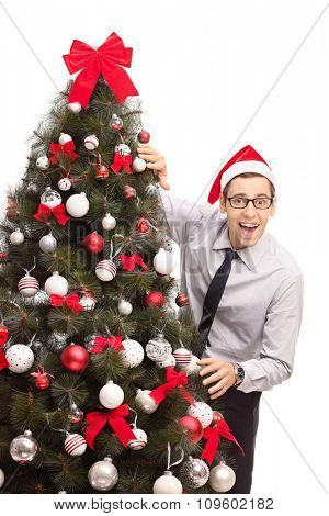 Vertical shot of a cheerful guy with Santa hat standing next to a Christmas tree and looking at the camera isolated on white background
