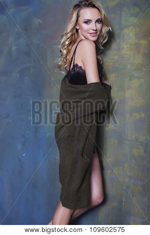 young pretty blond woman in warm sweater at home, winter coming, sexy long legs