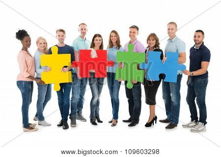 Creative Business People Holding Jigsaw Pieces