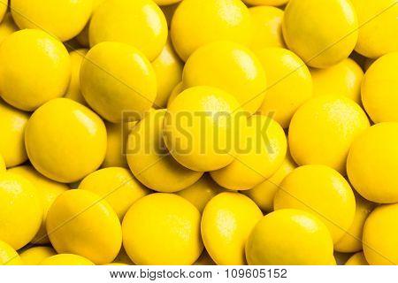 Close Up On Pile Yellow Milk Chocolate Candies Crisp Shell