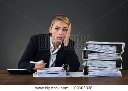 Stressed Businesswoman Looking At Folders While Working At Desk