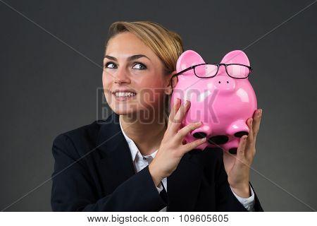 Businesswoman Shaking Piggybank Over Gray Background