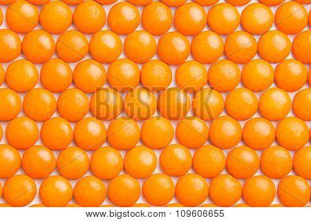 Close Up Neatly Arranged Orange Milk Chocolate Candies Crisp Shell