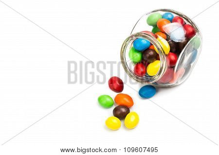 Transparent Glass Jar With Colorful Chocolate Candies On White Background