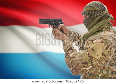 Male In Muslim Keffiyeh With Gun In Hand And National Flag On Background - Luxembourg