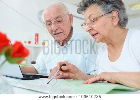 Couple looking at map and laptop