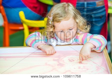 Cute Child Girl Drawing Draws Developing Sand In Preschool At Table In Kindergarten