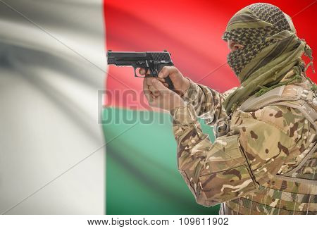 Male In Muslim Keffiyeh With Gun In Hand And National Flag On Background - Madagascar