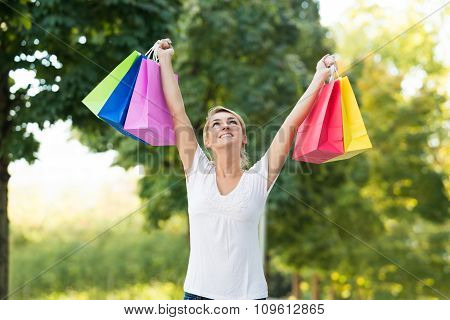 Woman With Arms Raised Carrying Shopping Bags