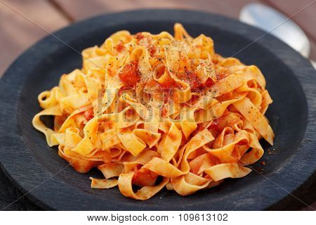 Tagliatelle with tomato sauce in wooden plate, close-up