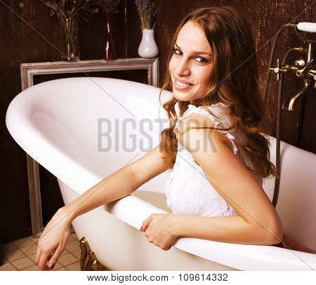 young pretty real brunette girl enjoying bath with foam
