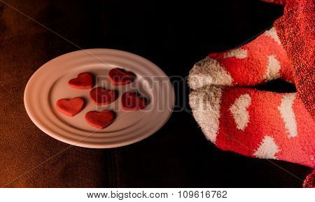 Feet in socks with hearts and cookies in shape of heart