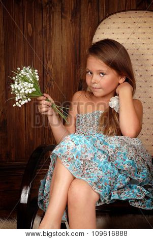 Girl with a bouquet lilies of the valley in chair