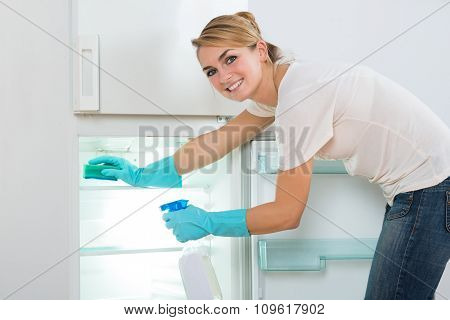 Smiling Woman Cleaning Refrigerator With Sponge And Spray