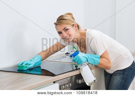 Confident Woman Cleaning Induction Stove At Home