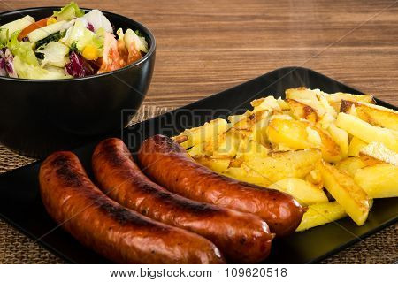 Grilled sausages and fried potatoes on the black plate on the rustic surface.