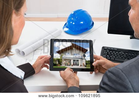 Two Architects Looking At House On Digital Tablet