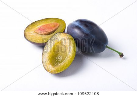 Group Of Plums With Halfs And Slices On White Background